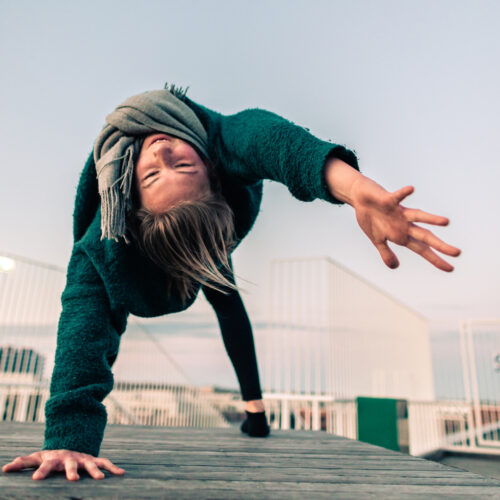 Camilla practicing yoga on a rooftop at sunrise. She's doing a wild thing and working on fulfillment in her yoga practice