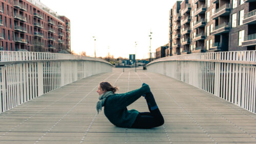 Camilla practicing yoga on a rooftop at sunrise. She's doing a bow pose and working on fulfillment in her yoga practice
