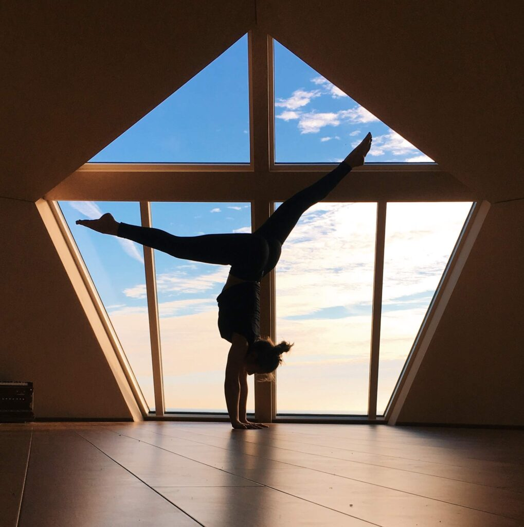 Handstand silhouette in front of huge window