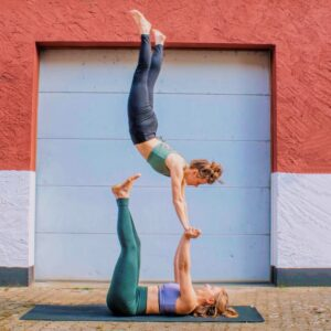 Julia and Camilla doing an acroyoga pop showing what acroyoga teaches people - namely to trust each other.