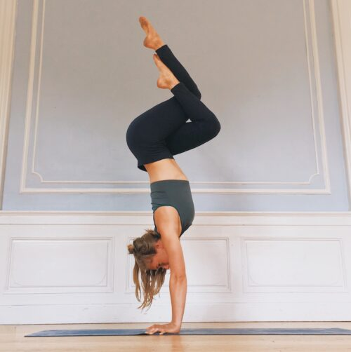 Camilla doing a handstand in her home yoga practice