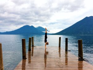 Complete handstand guide picture of Camilla handstanding on a bridge overlooking the volcanoes surrounded Late Atitlan in Guatemala