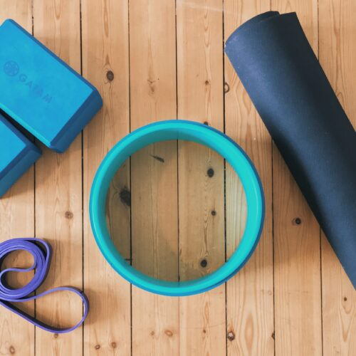 Camillas yoga props that she uses in her home yoga practice - two yoga blocks, a yoga wheel, a yoga mat, and a yoga strap.