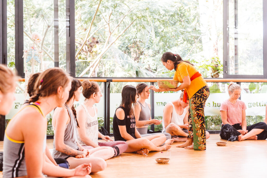 my 200 hour vinyasa yoga teacher training bali at Ubud Yoga centre - getting a blessing from balinese woman
