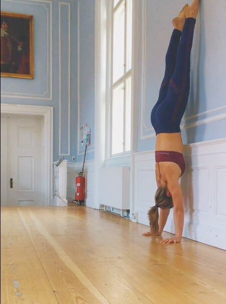 Belly to wall handstand exercise