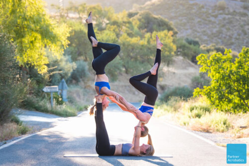Camilla, Iris, and Louise performing an acroyoga trio pose demonstrating what acroyoga is