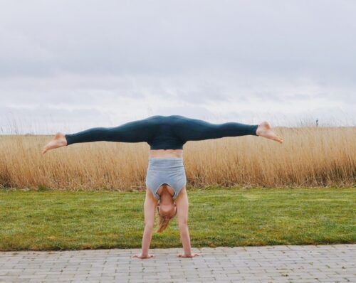 Camilla doing a freestanding straddle pike handstand seen from the front