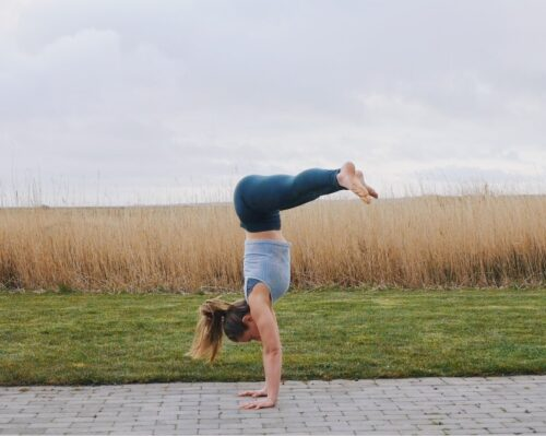 Camilla doing a freestanding straddle pike handstand seen from the side