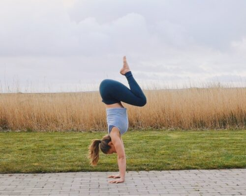 Camilla doing a tuck shaped handstand with the knees tucked in to the chest.