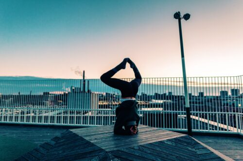 Camilla practicing yoga on a rooftop at sunrise. She's doing a headstand and working on fulfillment in her yoga practice